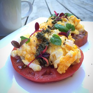Beefsteak tomatoes toped with scrambled eggs and pesto